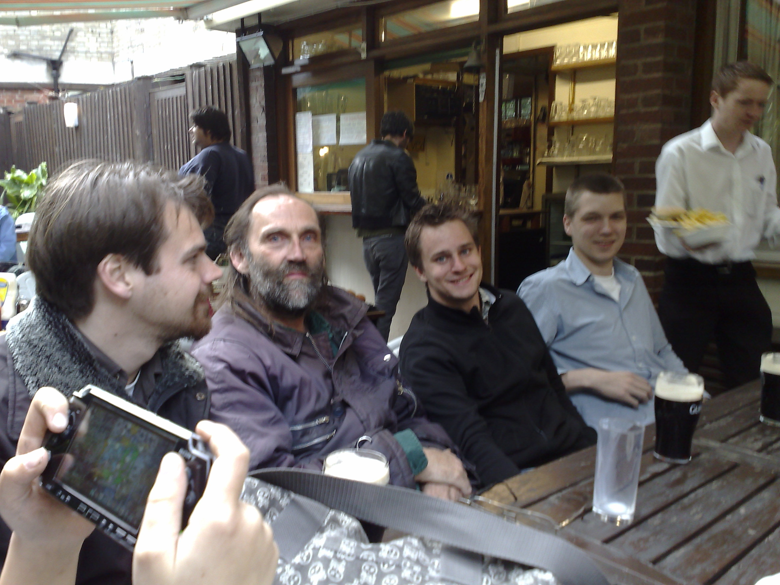 Mark, Kees, Tim and Julain relax and chat with their fellow Stratego players outside a local bar.